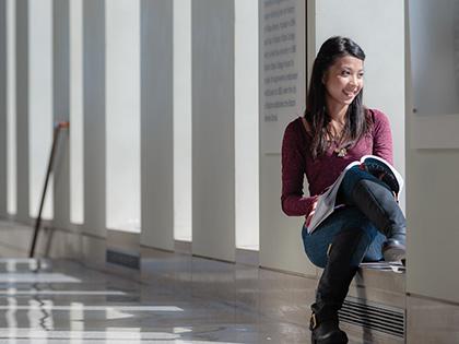 女学生坐在那里,手里拿着一本课本,微笑着凝视着窗外