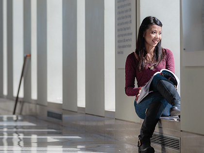 Female student sitting holding a text book staring out the window and smiling