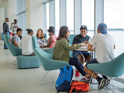 Three students sitting and chatting at round table next to window