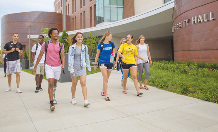 Eight students walking past University Hall in summer