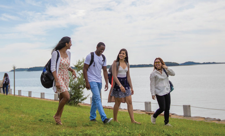 Four students walking on the grass next to the river