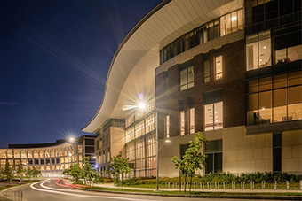 UMass Boston building at night with light shining outside