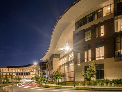 Modern UMass Boston building at night with light shining out front